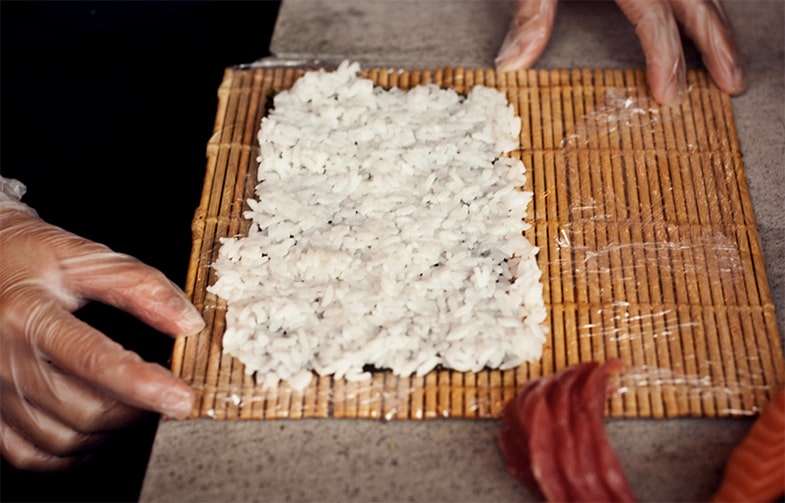 Sushi-Reis auf Sushi-Matte
